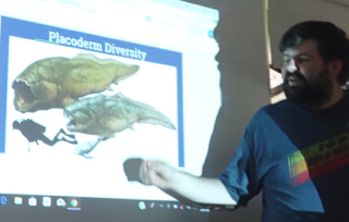 Photo of Robbie Stewart with illustration of Devonian period Placoderm fish