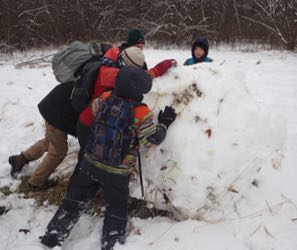 Photo of four Macoun Club members rolling a snowball more than a meter in diameter