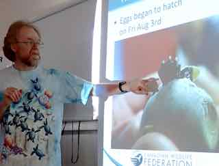 Photo of David Seburn with picture of turtle egg in the act of hatching