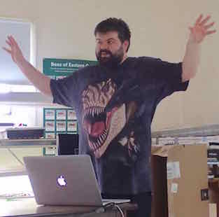 Photo of Robbie Stewart with arms spread wide, wearing T-rex T-shirt