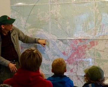 Photo of Macoun Club leader Rob Lee showing Macoun Club members the topographic features of the Ottawa region on a wall map