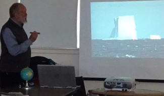 Photo of Roy John showing his picture of Antarctic iceberg