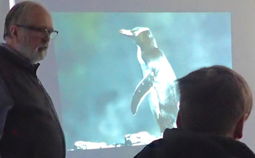 Photo of Roy John showing picture of penguin to Macoun Club member