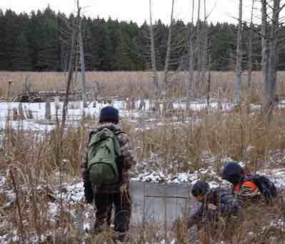 Photo of Macoun Club members poking at new ice on Pond VI