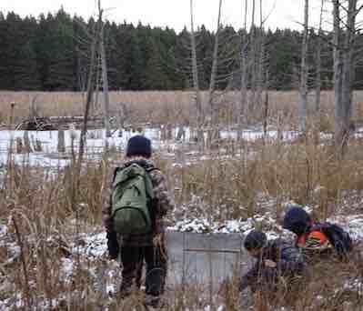 Photo of Macoun Club members poking at new ice on Pond VI