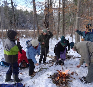 Photo of Macoun Club group at lunch fire in the woods