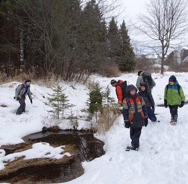 Photo of Macoun Club group poking around open water in winter