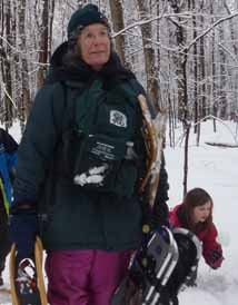 Photo of Diane Kitching burdened with snowshoes