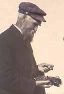 Photo of John Macoun examining bird nest