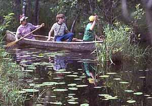 Photo of Macoun Club leader Martha Camfield in the stern of a canoe, with members Lorin Gaertner and Amber Stewart, ca. 1988