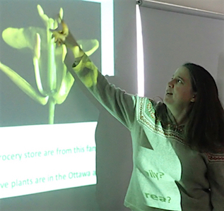 Photo of Jen Line pointing out stamen structure at a Macoun Club meeting