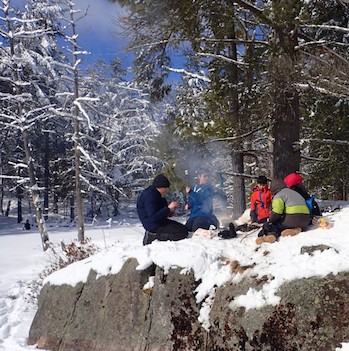 Photo of Macoun Club members eating lunch in the sunny, snowy woods