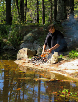 Photo of Macoun Club member Samantha tending her own campfire