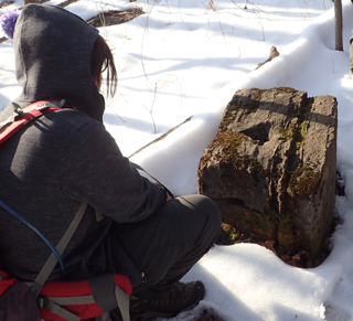 Photo of Macoun Club member examining limestone block tipped up on edge