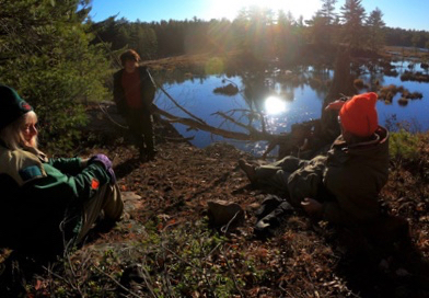 Photo of Macoun Club group seated above lake in autumn sunshine