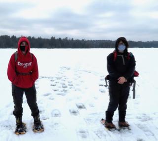 Photo of Macoun Club members (wearing masks because of COVID-19 concerns) on slushy lake ice