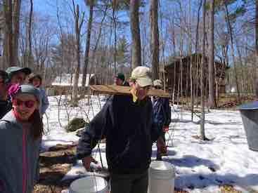 Photo of Macoun Cub leader Rob Lee carrying sap buckets