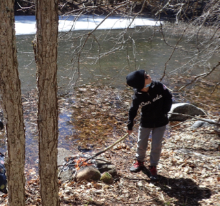 Photo of Macoun Cub member at campfire by pond, craning neck to see a passing bird